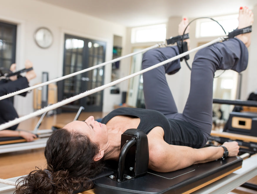 Group Reformer Pilates class with props